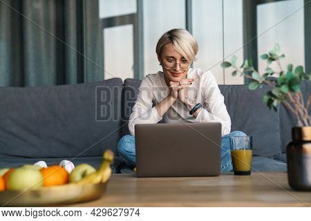 Smiling mid aged blonde woman studying online via laptop computer in the living room