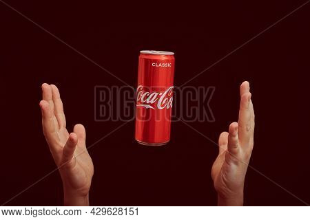 Kaliningrad, Russia - March 13, 2021 - Hands Catch Coca Cola Can, Red Background. Classic Coke Jar,