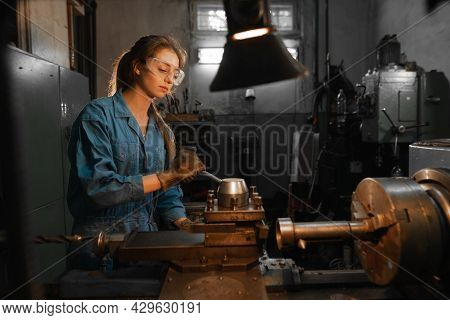 A Young Woman In Goggles And Overalls Is Standing Near The Lathe. Profession Concept Turner, Metalwo
