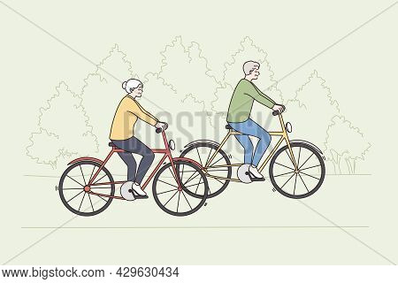 Happy Active Lifestyle Of Old People Concept. Mature Elderly Couple Man And Woman Riding Bicycles To