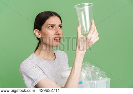 Young confused frowning woman carrying a plastic container full with empty recyclable plastic. Recycling concept