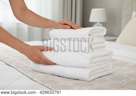 Woman Putting Fresh Towels On Bed In Room, Closeup