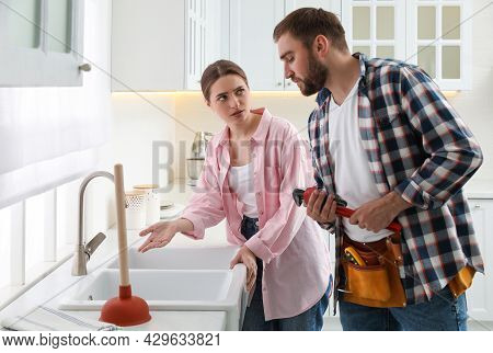 Young Woman Complaining To Plumber About Clogged Sink In Kitchen
