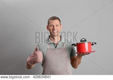 Happy Man With Cooking Pot On Light Grey Background
