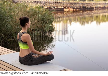 Woman Meditating On Wooden Pier Near River. Space For Text