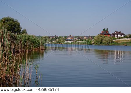 Reeds Along Banks Of River With River Houses Docked On The Opposite Side Reflecting In Still Waters.