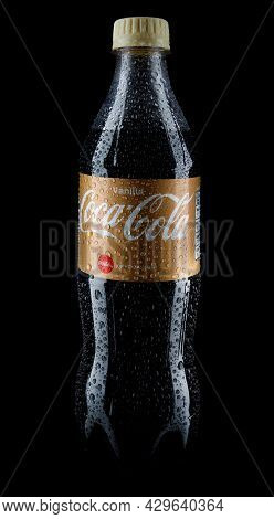 A Bottle Of Vanilla Coca Cola Is Isolated On A Black Background. Water Drops On A Coca-cola Bottle.