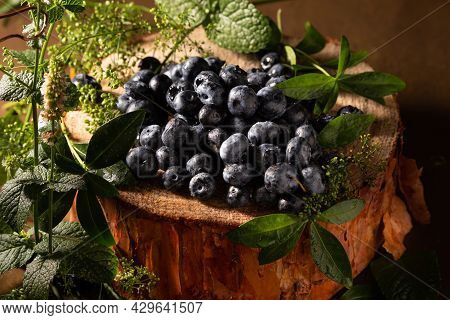 Ripe Blueberries And Mint On Brown Background