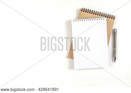 Two Blank Spiral Notepads Stacked On A White Background Next To An Automatic Pen. Notebooks With Whi