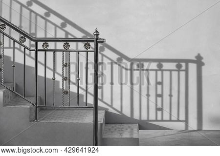 Stainless Steel Handrail Of Vintage Outdoor Staircase With Sunlight And Shadow On Cement Wall In Bla