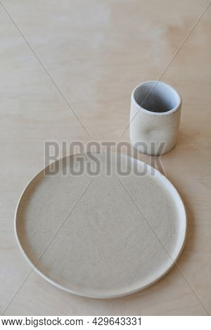 Ceramic Cup And Plates On A Wooden Table Top View. Minimalist Set Of Handmade Ceramic Tableware And