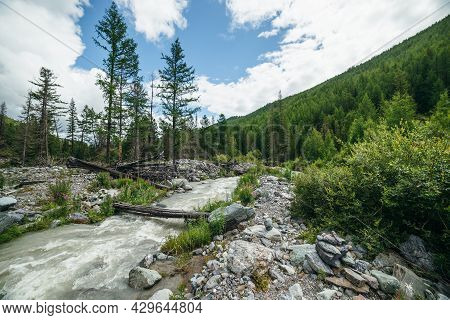 Beautiful Scenery With Log Bridge Across Powerful Mountain River Among Stones And Boulders Near Fore