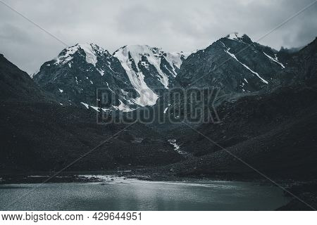 Dark Atmospheric Landscape With Mountain Lake Among Deep Black Rocks On Background Of Snowy Mountain
