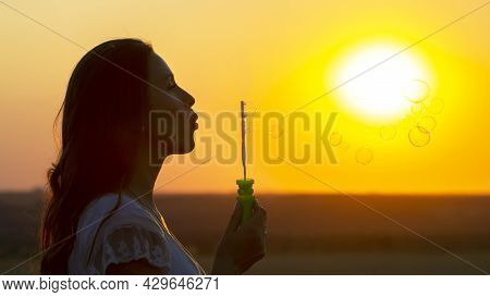 Woman Blows Bubbles Against The Backdrop Of The Setting Sun. Summer Fun And Outdoor Recreation