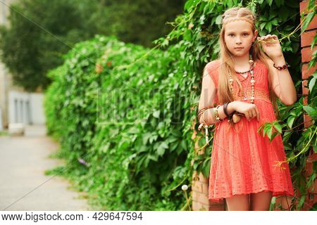 Portrait of a cute girl child dressed in hippie style posing against the background of green bushes. Romantic hippie style.