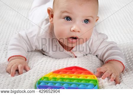Happy Kid Playing With Pop It. Newborn Baby Playing With Simple Dimple. The Flexible Sensory Fidget