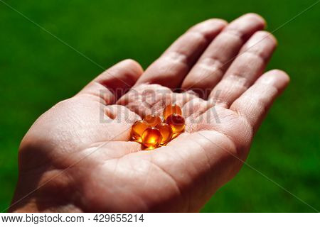 Top View On Womans Hands Holding Pile Of Capsules Omega 3