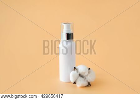 White Cosmetic Container With Dispenser And Natural Cotton On A Beige Background. The Concept Of Env