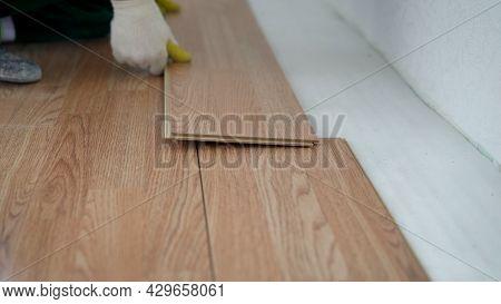 Home Renovate With Vinyl Laminate Flooring. Professional Construction Worker Installing New Vinyl La