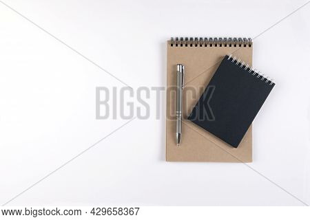 Two Blank Spiral Notepads Stacked On A White Background Next To An Automatic Pen. Notepads With Blac