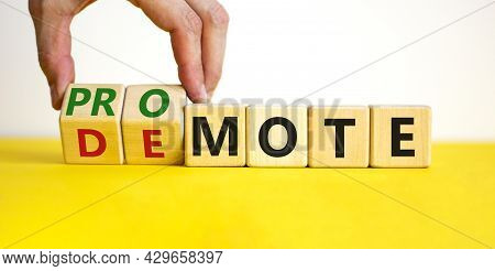 Promote Or Demote Symbol. Businessman Turns Cubes And Changes The Word 'demote' To 'promote'. Beauti