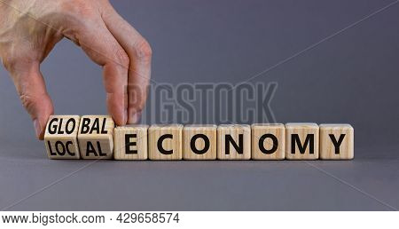 Local Or Global Economy Symbol. Businessman Turns Wooden Cubes And Changes Words 'local Economy' To