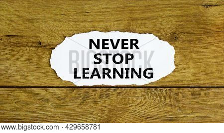 Never Stop Learning Symbol. Words 'never Stop Learning' On White Paper. Beautiful Wooden Background.