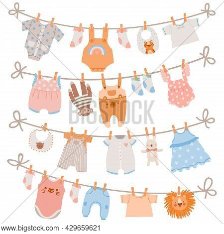 Baby Clothes On Rope. Newborn Children Apparel, Socks, Dress And Toys Hanging On Clothesline. Kids L