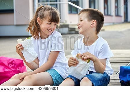 Schoolchildren Boy And Girl Laugh And Eat Their Lunch, Snack, Breakfast In The School Yard. Food For