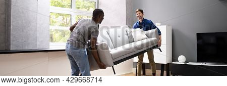 Couple Moving Furniture In Living Room. Carrying Sofa