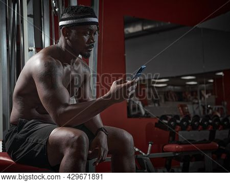 African American Athletic Man With Phone Using Sports App For Exercising And Gym Workout Sitting On