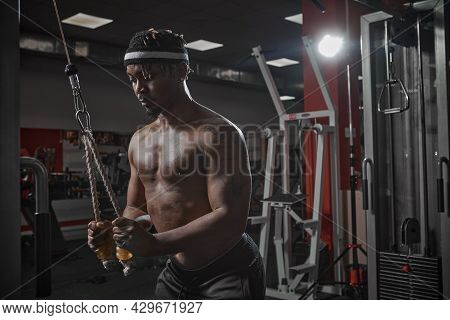 Concentrated African American Sportsman Training Muscles In Gym. Motivated Bodybuilder On Workout