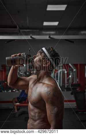 Sportive African American Man With Naked Torso Drink Water Or Sports Nutrition After Training In Gym