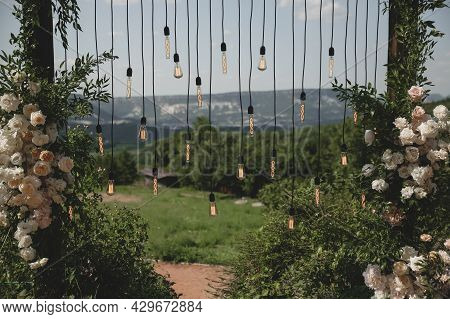 Wedding Arch On Boho Style With White Flowers In Park With Light Bulbs.