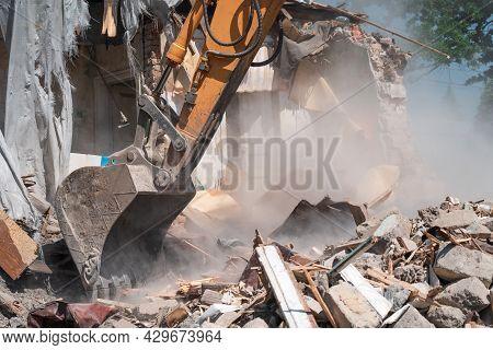 Hydraulic Excavator Bucket Breaks Down Old Building. Wreckage And Industrial Debris In Dust, House D