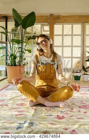 Young Female Gardener Meditating. Beautiful Girl Wear Jumpsuit And Earphones Relax After Study Or Wo