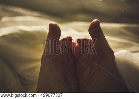 Female Naked Feet Lying In Fluffy Bed. Sleeping And Resting Comfort Concept. Joined Feet Enjoying Re
