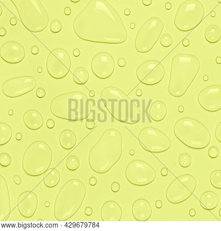 Water Drops On A Pastel Yellow Background. Water Texture Close Up. Backdrop Glass Covered With Drops