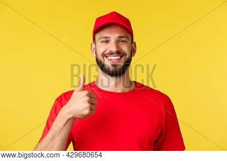 Close-up Of Cheerful, Optimistic Bearded Employee, Courier In Red Uniform, Show Thumbs-up, Encourage