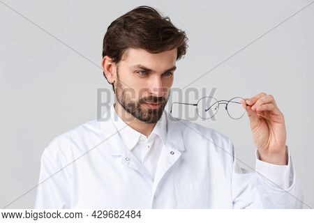 Hospital, Healthcare Workers, Covid-19 Treatment Concept. Close-up Handsome Bearded Doctor In Scrubs