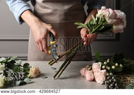 Florist Cutting Flower Stems With Pruner At Workplace, Closeup