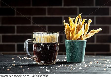 Mug Of Beer On Dark Background, Glass With Thick Foam, Dried Fish On Wooden Background. Beer Brewery