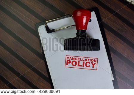 Red Handle Rubber Stamper And Cancellation Policy Text Isolated On Wooden Table.