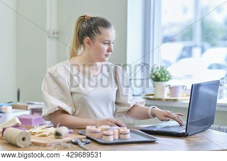 Small Business Owner. Portrait Of Mature Woman Standing At Her Shop Behind The Laptop And Smiling. F
