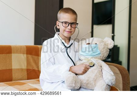 View Of A Child Playing Doctor Or Nurse With A Teddy Bear In The Sunlight At Home. Happy Boy Listens