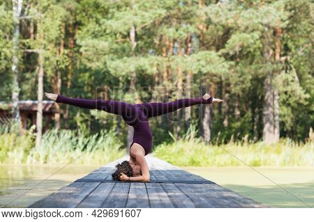 A Woman In Sportswear, Practicing Yoga In The Park, On A Mat Performs A Shirshasana Exercise With A