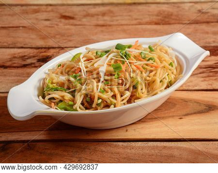 Veg Hakka Noodles A Popular Oriental Dish Made With Noodles And Vegetables, Served Over A Rustic Woo