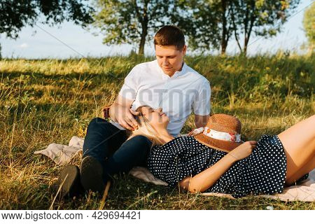 Happy Young Couple Resting On Blanket In Meadow, Beautiful Young Woman With Closed Eyes Lies On Lap
