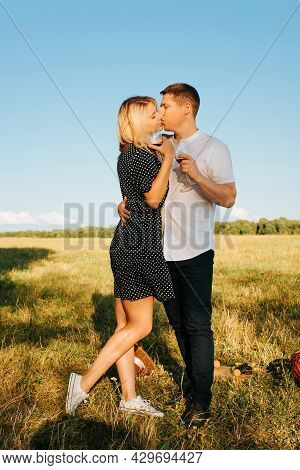 Young Beautiful Couple Hugs And Kisses Tenderly, Hold Glasses With Red Wine, Field At Sunset. Fashio