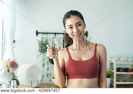 Portrait Of Asian Attractive Woman Pour Water Into Glass In Kitchen. Young Thirsty Beautiful Sport G